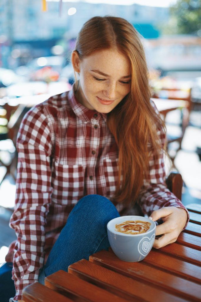 Girl with big cup of coffee at a wooden table outdoors