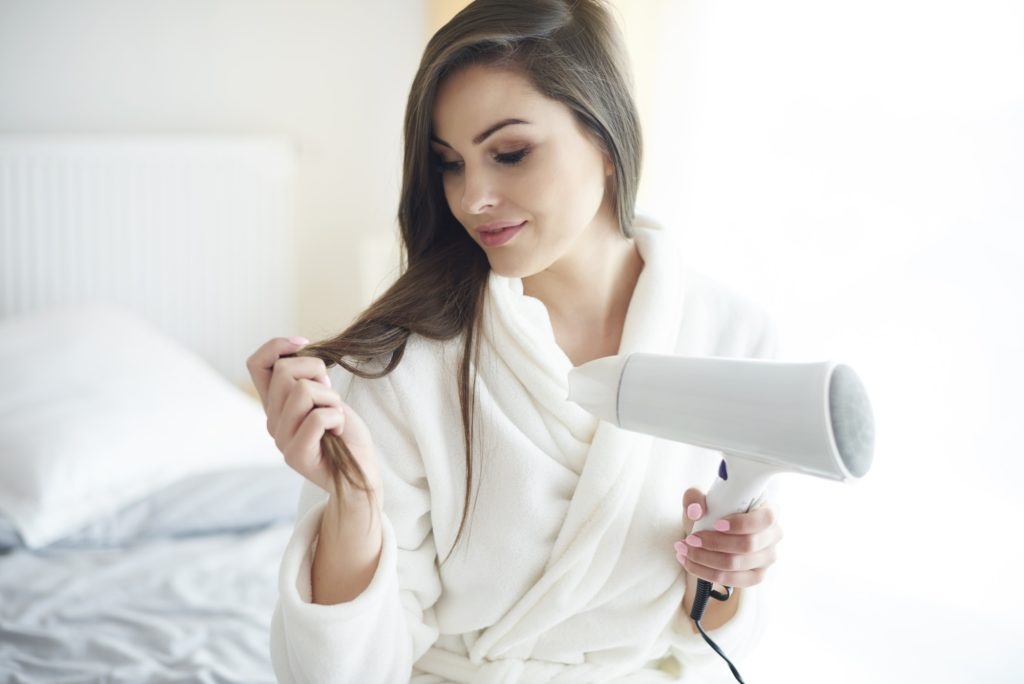 Close up of woman with hair dryer